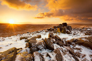 Golden sunrise over snow covered Belstone Tor, Dartmoor