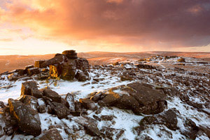 Fiery sunrise over snow covered Belstone Tor, Dartmoor
