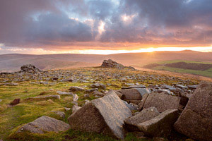 Glimpse of the sun as it sets over Higher Tor, Dartmoor