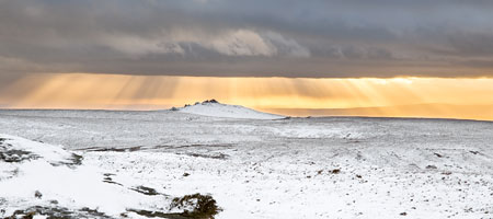 Golden sunrays over snow covered Great Links Tor, Dartmoor