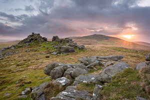Sun peeks out from behind the clouds over West Mill Tor, Dartmoor